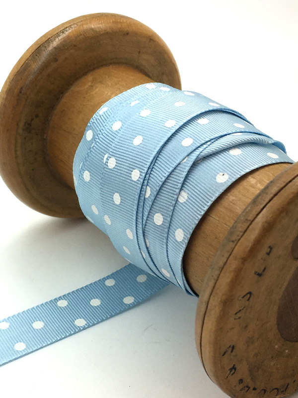 A vintage style, pale blue ribbon with white polka dots