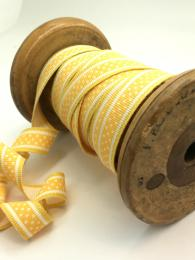 A yellow ribbon with white stripes and polka dots