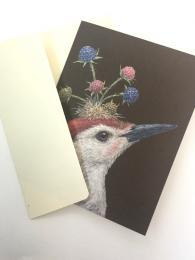 A quirky greetings card featuring a woodpecker with berries growing from his head