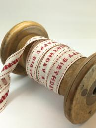 A red and white ribbon saying 'happy birthday' in a cross stich style