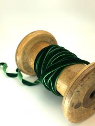 A thin, green velvet ribbon, perfect for wrapping gifts or craft projects.